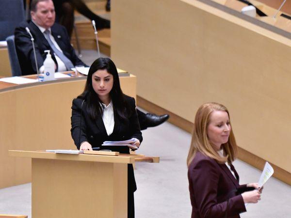 Vänsterpartiets ledare Nooshi Dadgostar och Centerpartiets ledare Annie Lööf, med statsminister Stefan Löfven i bakgrunden.
